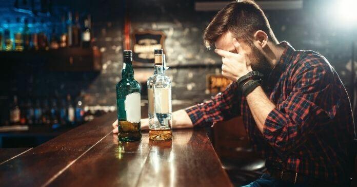 Alcoólatra sentado no bar consumindo bebida destilada