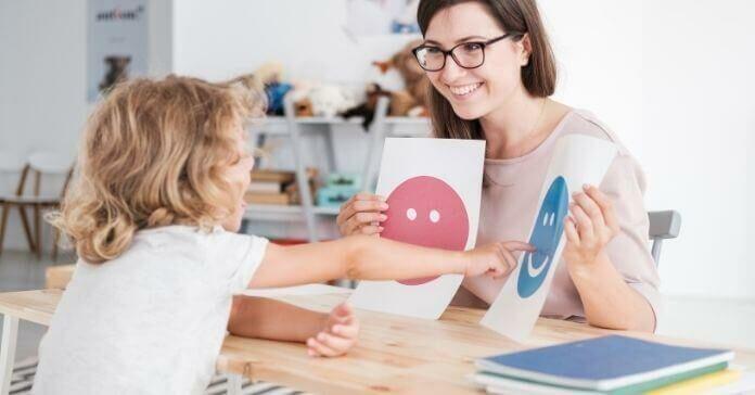 Conselheira sorridente segurando fotos durante reunião com jovem paciente com autismo
