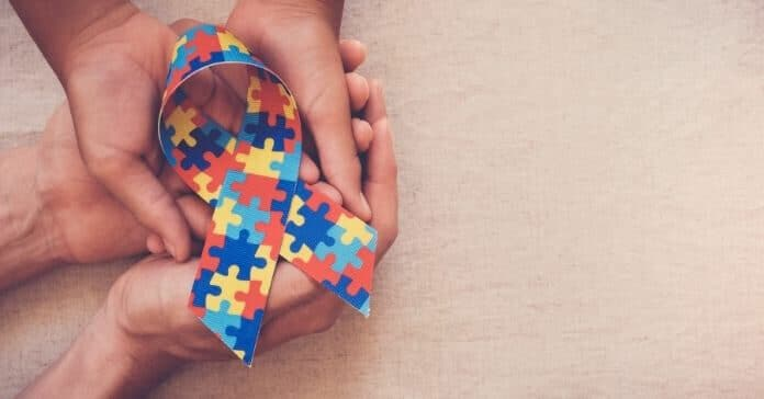 Mãos segurando uma fita de quebra-cabeça para conscientização do autismo
