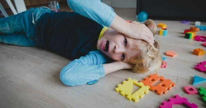 Menino triste gritando com brinquedos espalhados, criança estressada